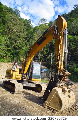 excavator  on a construction site of the road in the mountain - stock photo