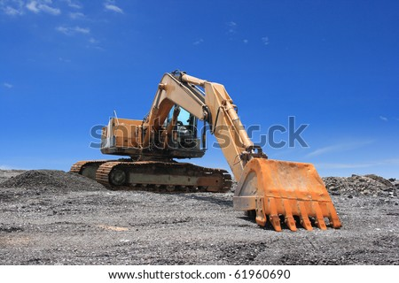 Excavator on blue sky - stock photo
