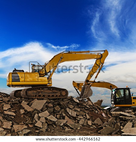 Excavator on construction site with blue sky - stock photo