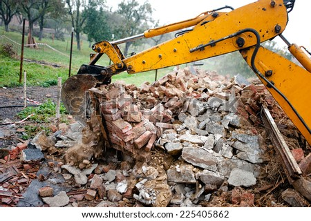 excavator on demolition site loading bricks and concrete walls - stock photo