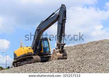 Excavator on Stone Drum against blue cloudy sky