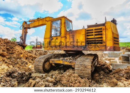 Excavator on the construction site beneath blue cloudy sky - stock photo