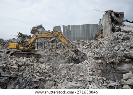 Excavator on the ruins of the building - stock photo