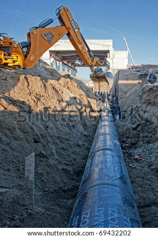 Excavator set steel pipe in a trench - stock photo