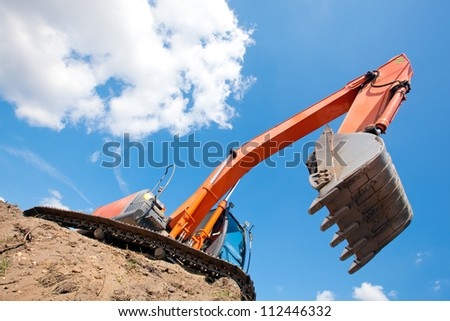 Excavator standing in a ground with raised bucket over blue cloudy sky - stock photo
