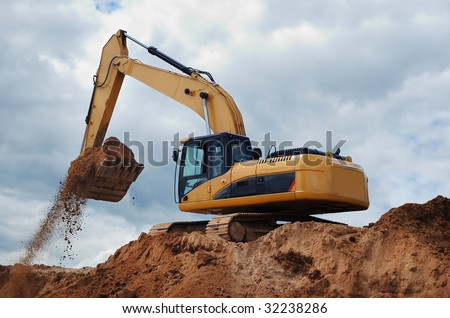 Excavator standing in sandpit is moving earth by its bucket - stock photo