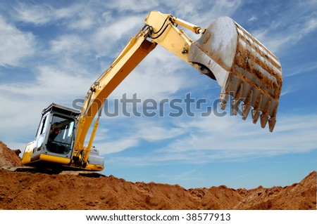 Excavator standing in sandpit with raised bucket over cloudscape sky - stock photo
