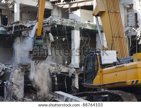 Excavator with demolition grapple demolishing building - stock photo