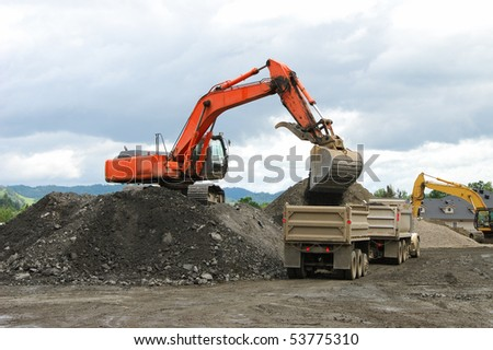 Excavator working a spoils pile at a new building site in Roseburg Oregon - stock photo