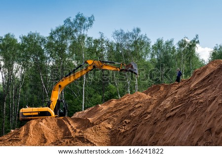 Excavator working on a mountain of sand - stock photo