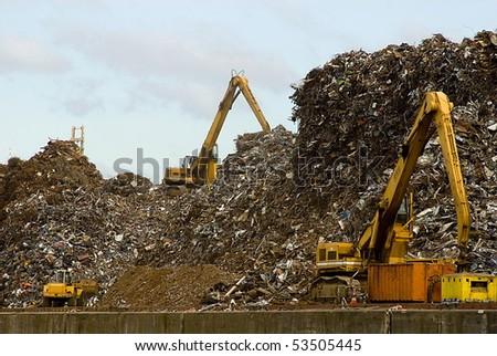 excavators works on a garbage dump - stock photo