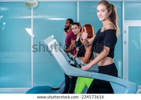Excellent sports. Sport and slender girl running on a treadmill and shows thumb up. Athlete dressed in sports uniforms and running in the gym. - stock photo