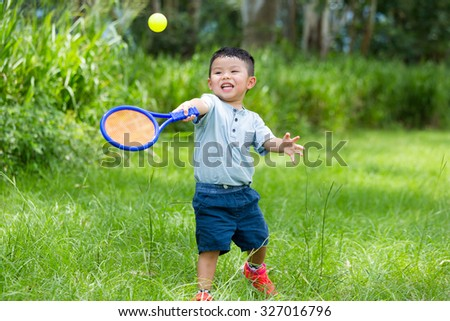 Excite Little boy play with tennis at park - stock photo