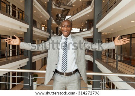excited african businessman with arms outstretched in modern office building - stock photo