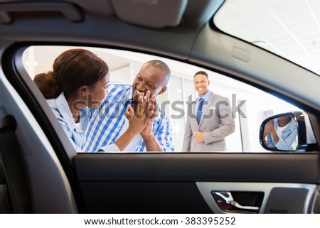 excited african couple at the dealership buying new car - stock photo