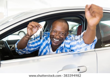 excited african man showing a car key inside his new vehicle - stock photo