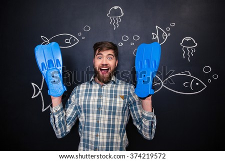 Excited amusing young man with blue flippers on hands standing over drawing of underwater world on blackboard background - stock photo