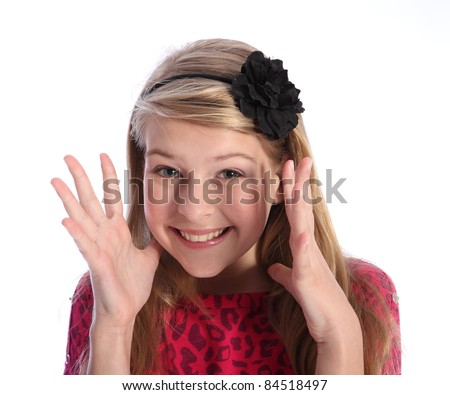 Excited and pleased young pretty caucasian school girl with happy smile, hands on her face. She has blonde hair and a black flower hair band.