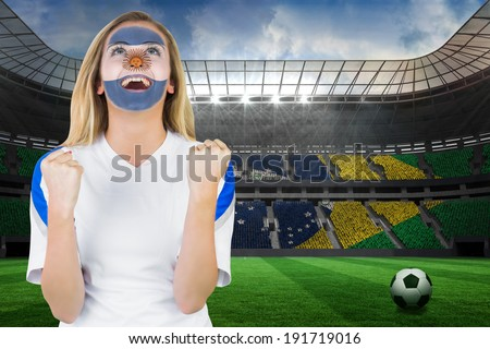 Excited argentina fan in face paint cheering against large football stadium with brasilian fans - stock photo