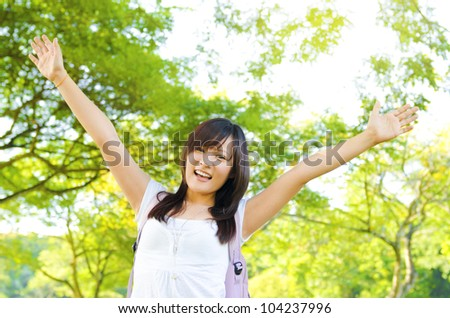 Excited Asian teen raise her arms in university campus - stock photo