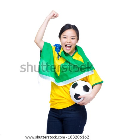 Excited asian woman draped with Brazil flag and holding soccer ball