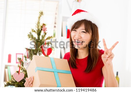 Excited Asian woman getting her Christmas present, showing peace hand sign, indoor/inside her home. - stock photo