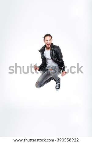 Excited attractive young man screaming and jumping over white background - stock photo