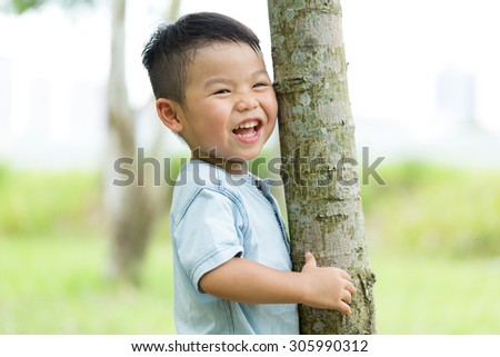 Excited Baby boy hold with tree bark - stock photo