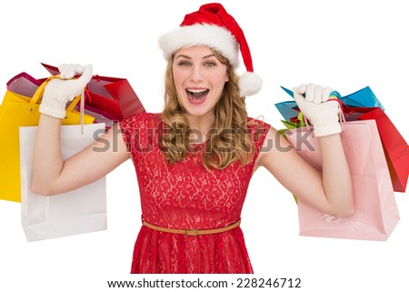 Excited blonde in santa hat holding shopping bags on white background