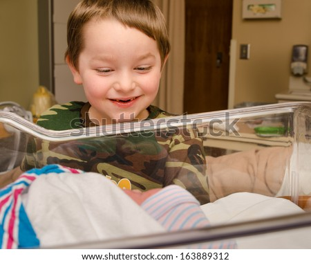 Excited boy meets his infant sibling for the first time after delivery at hospital - stock photo