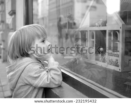 Excited boy next to storefront propping his head in hands, monochrome                                     - stock photo