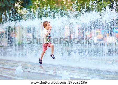 excited boy running between water flow in city park - stock photo