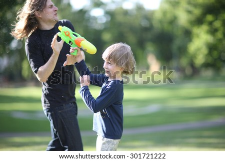 Excited boy spraying his father with water - stock photo