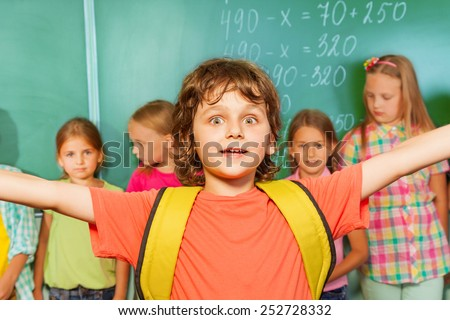 Excited boy with arms apart wears yellow bag near chalkboard and other students during mathematics class - stock photo