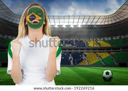 Excited brasil fan in face paint cheering against large football stadium with brasilian fans - stock photo
