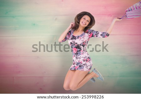 Excited brunette jumping while holding shopping bag against pink and green planks - stock photo