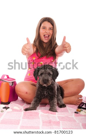 excited brunette teenage girl in swimsuit with her shipoo dog showing thumbs up gesture inviting people to go to the beach (studio setting with beach and personal items) isolated on white background