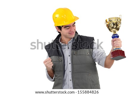 Excited builder holding trophy - stock photo