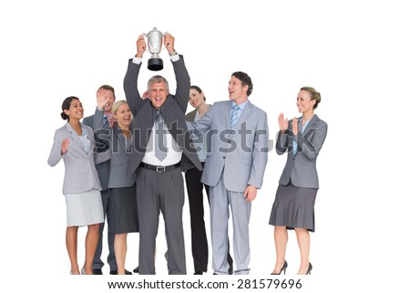 Excited business team cheering at camera with trophy on white background - stock photo