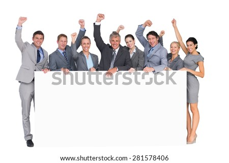 Excited business team holding poster on white background - stock photo
