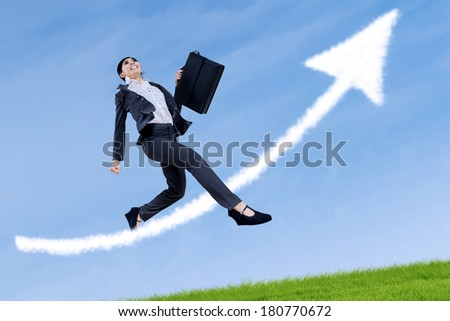 Excited business woman jumping and holding a briefcase with arrow sign