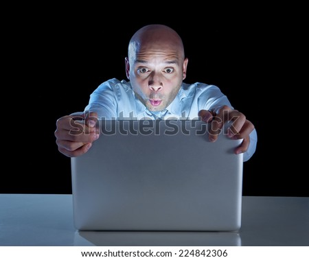 excited businessman alone at night sitting at computer laptop watching porn or online gambling isolated on black background on internet addiction concept  - stock photo