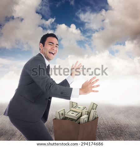 Excited businessman catching against blue sky - stock photo