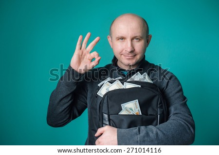 excited businessman holding bag with money and smiling. - stock photo
