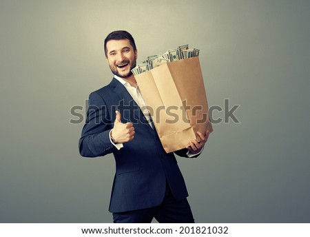 excited businessman holding paper bag with money, showing thumbs up and smiling. photo in studio over grey background - stock photo