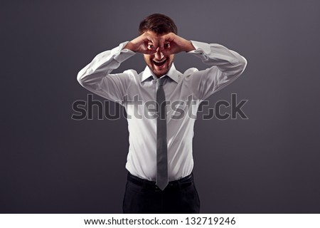 excited businessman looking through imaginary binocular. studio shot over dark background - stock photo