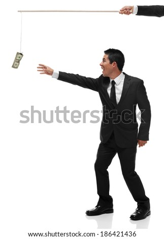 Excited businessman reaching for money on the end of a stick being bribed full body - stock photo