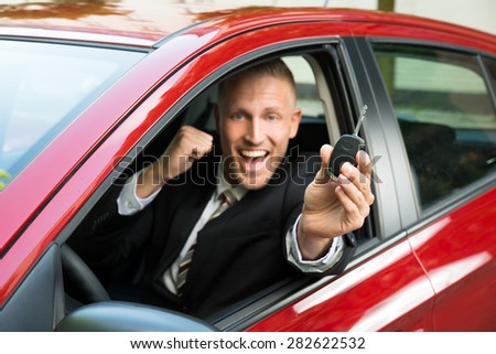 Excited Businessman Sitting In A Car Showing New Car Key - stock photo