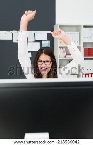 Excited Businesswoman at Desk Celebrating with Arms in Air - stock photo