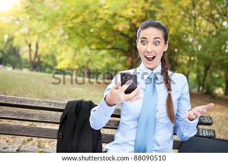 excited businesswoman reading text message on phone, outdoor - stock photo